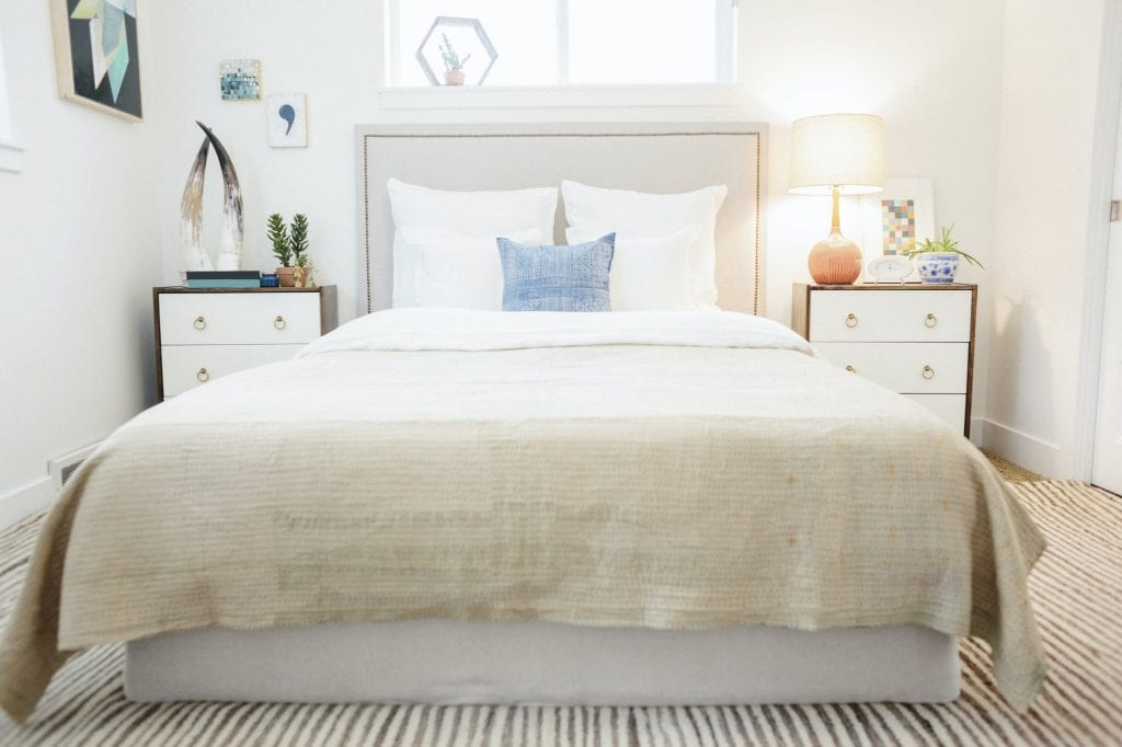 A bedroom in an apartment with a double bed and beside cabinets, and a plain cream quilted bedspread