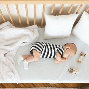Cute infant baby napping on his side in wooden cot